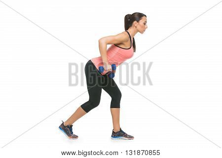 Beautiful sporty woman in sportwear making exercise with blue dumbbells. Isolated over white background. Copy space.
