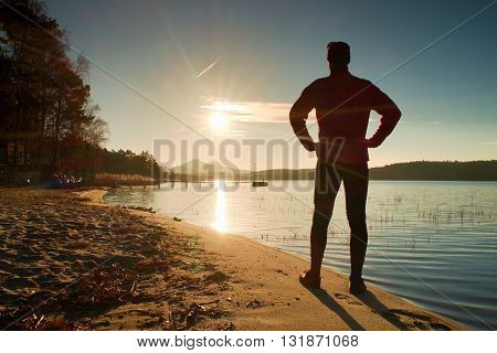 Silhouette Of Tall Sportsman On Decline Seeing Over Bay To Sun