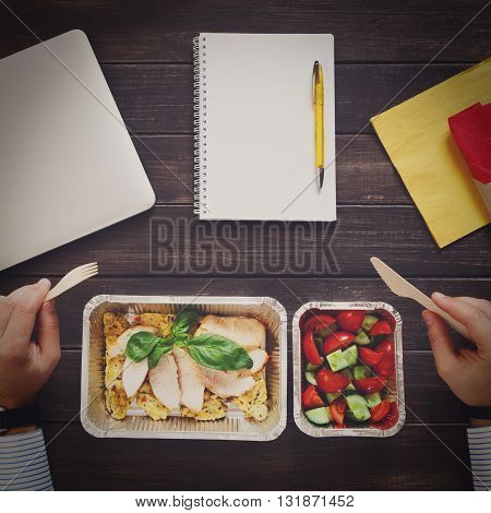 Healthy eating man. Business lunch at working place. Healthy, diet food take away in aluminium boxes: roasted turkey with salad. Top view of hands with fork and knife, flat lay at office table