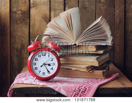 Red retro alarm clock and a stack of books on the table. An open book. Still life with books.