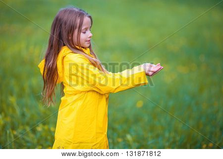 Adorable little girl happy standing under the rain outdoors