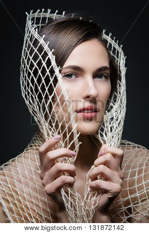 Beautiful young woman with rough net. Natural makeup. Fashion beauty shot over dark background.