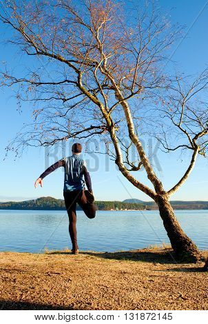 Silhouette Of Sport Active Man In Running Leggins And Blue Shirt At Birch Tree On  Beach. Calm Water
