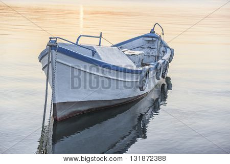 Fishing boat on the sea water at sunset.