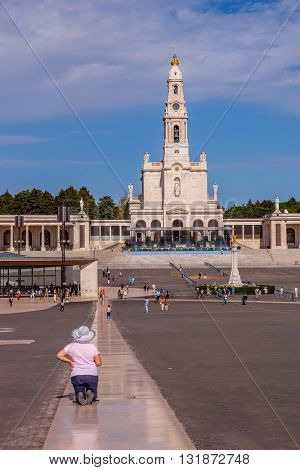 FATIMA, PORTUGAL - SEPTEMBER 9, 2011: The religious woman in hat is kneeling specially constructed path. The square in front of a Catholic cathedral with tourists and believers