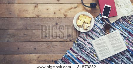 Top view of breakfast table with smartphone and open book.
