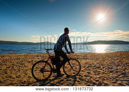 Young Man Cyclist Silhouette On Blue Sky And Sunset Background On The Beach. End Of Season At Lake.