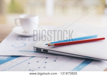 Closeup of coffee cup business review pencils and laptop on office desktop