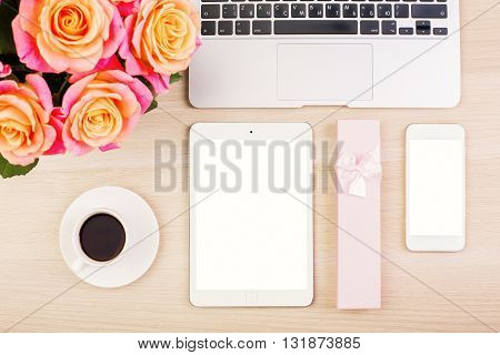 Top view of designer woman's desktop with blank white smart phone and tablet gift case coffee cup roses and laptop keyboard. Mock up