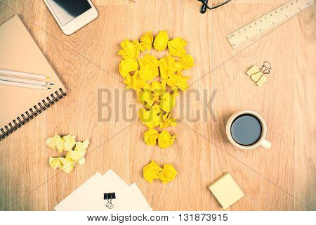 Top view of wooden desktop with crumpled paper lightbulb coffee smartphone and various stationery items. Idea concept