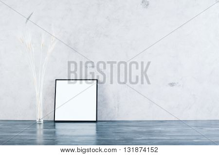 Small square picture frame and wheat spikes on concrete background. Mock up
