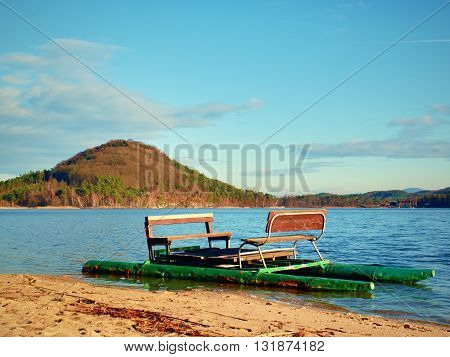 Abandoned Old Pedal Boat Caught On Sea Sandy Beach At Sunset. Island With Forest At Horizon.