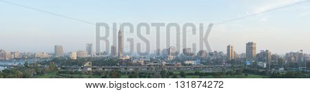 Cairo Egypt - May 22 2016: Wide panoramic view of central Cairo skyline at dusk the Nile river the Island of Zamalek and the 6th October Bridge.