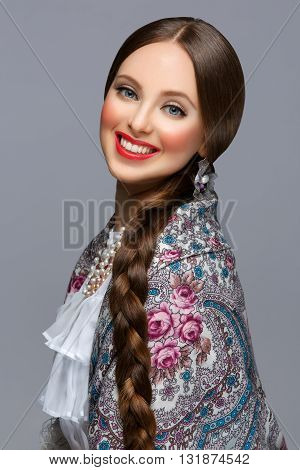 Happy beautiful young russian woman with very long braid in traditional shawl. Red lips. Over grey background.