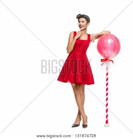 Beautiful young woman in red dress with huge lollipop candy. Surprised expression. Isolated over white background. Copy space. Square composition.