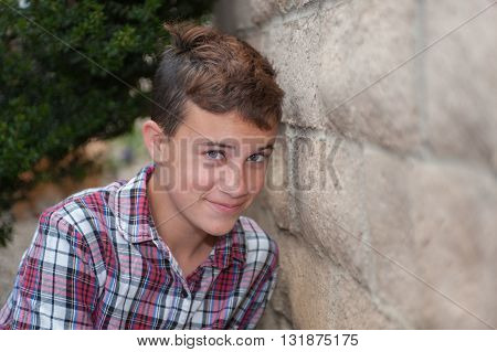 Pretty girl with very short haircut against wall.