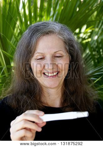 Middle-aged woman looking happy while seeing the results of a home pregnancy test.
