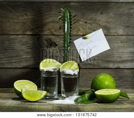 Tequila with lime and salt on a wooden background