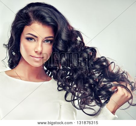 Model brunette with long curly hair .  Wavy hairstyle