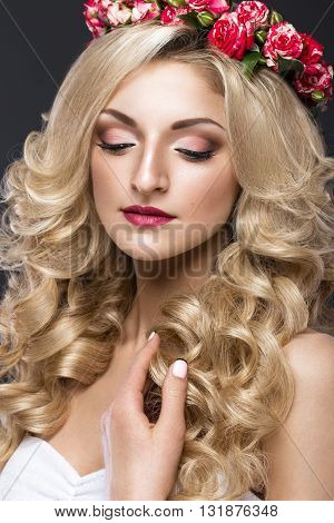 Portrait of a beautiful blond girl in image of the bride with purple flowers on her head. Beauty face. Photo shot in the Studio on a grey background
