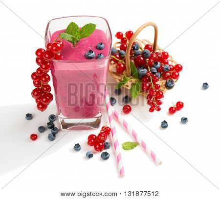 Smoothie milkshake of berry (redcurrant blueberry) in a glass and fresh berries in a basket isolated on white background.