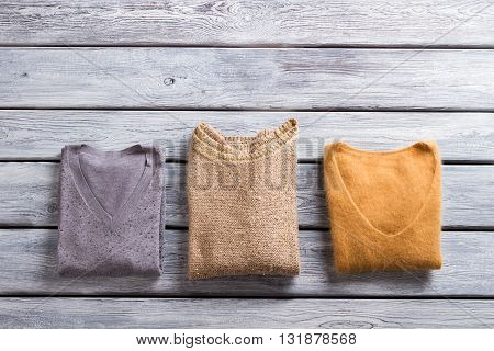 Folded sweaters of different color. Casual pullovers with v-neck. Warm garments on gray shelf. Quality autumn clothes for girls.