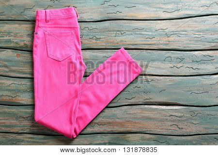 Pink casual pants. Folded trousers on wooden background. Woman's pants on green shelf. Garment bought at auction.