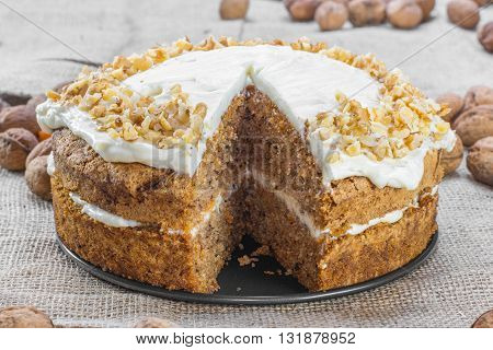 Cut Carrot and Walnut Cake Topped with Cream on Jute Background with Walnuts