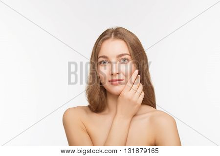 Studio shot of beautiful shirtless lady touching her face skin and looking ar camera over white background in studio.