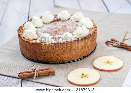 Apple Pie with Whipped Cream with Cinnamon and Apple Slices on White Table
