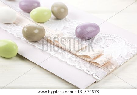 Colored sugared almonds and wedding paper on white wooden background