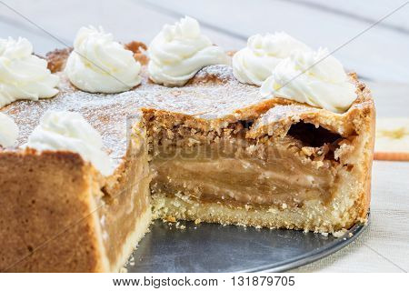 Detail on a Sliced Apple Pie with Whipped Cream with Cinnamon and Apple Slices on White Table