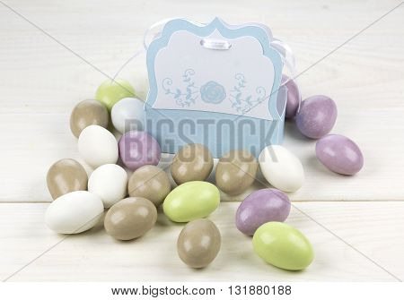 Colorful sugared almonds and papery box on white wooden background