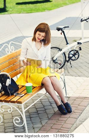 Girl surf internet from tablet PC outdoors in the park. Girl with gadget and bicycle. Student girl on the bench. Rest, leisure with gadgets in the park. Cycling and resting.