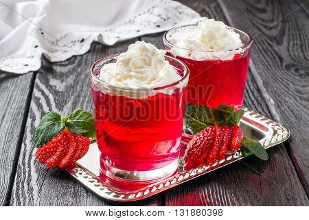 Delicious strawberry jelly with whipped cream in a glass and ripe strawberries on a metal plate on dark wooden table. Selective focus