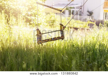 Abandoned swing at high grass in the spring season