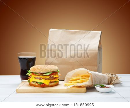 Fast food. Hamburger, potato fries, cola drink. Takeaway food. Wrapped French fries, packaging, Cola glass, tomato sauce, double cheese hamburger at rustic wood and red background.