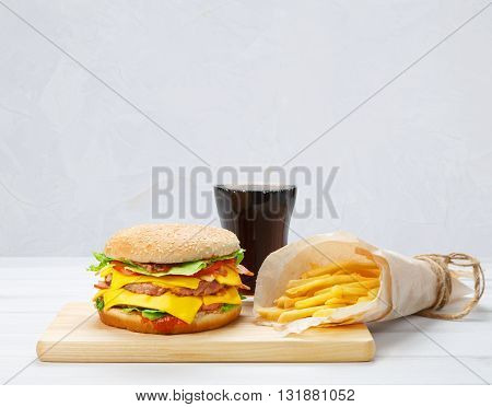 Fast food. Fast food meal with copyspace. Hamburger, potato fries, cola drink. Takeaway food. Wrapped French fries, packaging, Cola glass, tomato sauce, double cheese hamburger at wood.