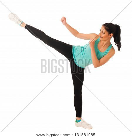 Karate woman kicks with her leg high in copy space
