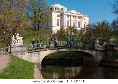 PAVLOVSK, ST. PETERSBURG, RUSSIA - MAY 8, 2016: People on the Centaur bridge against Pavlovsk palace. The bridge was built in 1795-1797 by design of Vincenzo Brenna