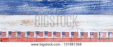 Small USA flags on bottom of red white and blue rustic boards. Fourth of July holiday concept for United States of America.