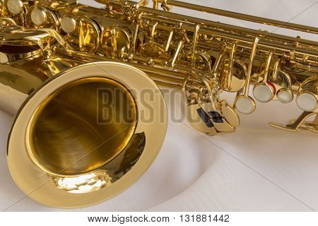 beautiful golden saxophone on delicate White silk background