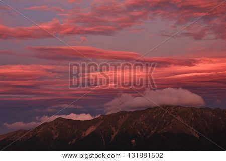 Colorful sky over a mountain range in New Zealand. View from Mt Robert.