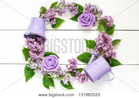 Colorful wreath of lilac with decorative watering can bucket and candles . Use for floral backgrounds holiday greetings and invitations postcard. Top view space for text