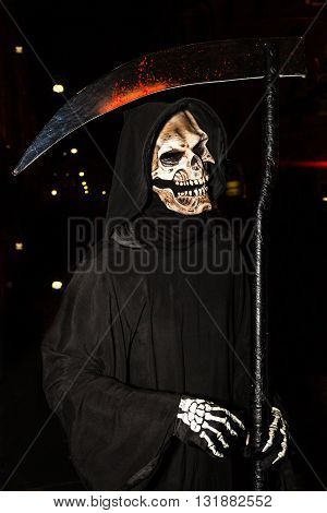 Portrait of the face of death with a scythe for Halloween by night.