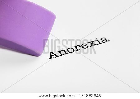 Anorexia word with eraser on white paper background