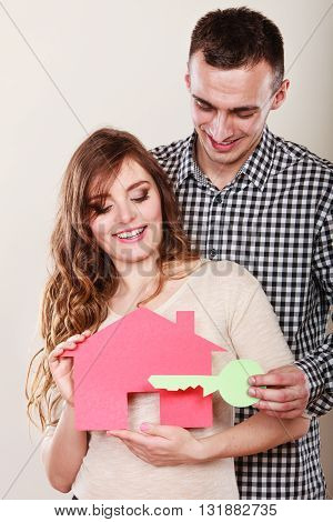 Smiling young couple holding paper house and key. Husband and wife dreaming about new home. Housing and real estate concept.
