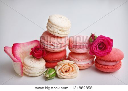 Macaroons with roses on white background