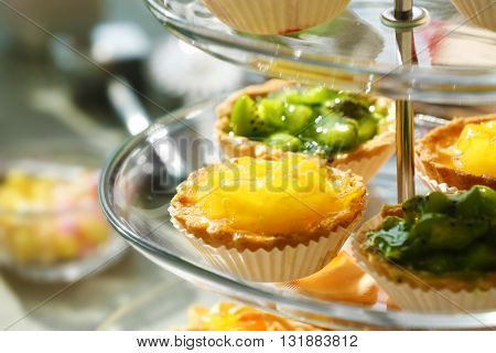 Fresh homemade fruit tarts with citruses and kiwi on a white table.