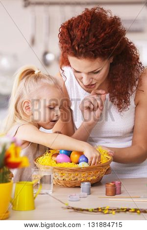 Mother and daughter decorating Easter eggs in the kitchen